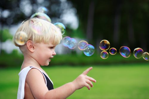 1 year old boy pointing at bubbles