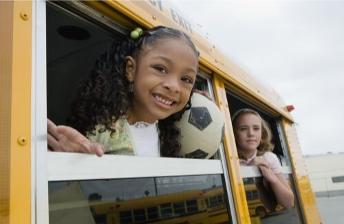 6 year old girl looking out school bus window holding soccer ball