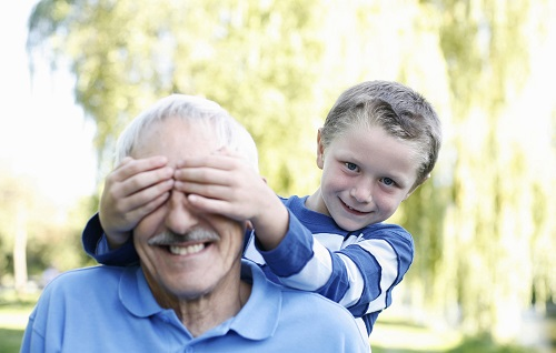 a smiling 55 year old man with a kid covering his eyes