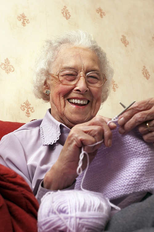 Old woman smiling and knitting