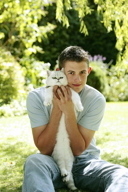 18 year old man with cat looking at camera
