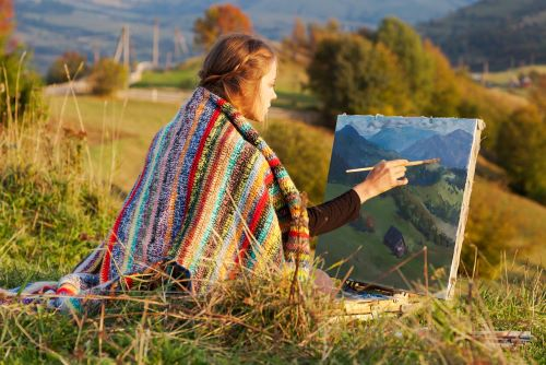 artist outside painting landscape