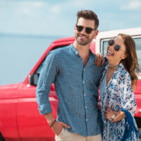 man and woman standing outside of a red jeep