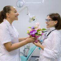 female dentist handing another female dentist a vase of flowers