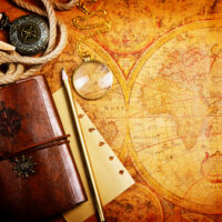 old notebook, loupe and compass on the map