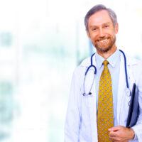 older male doctor smiling