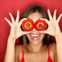 woman holding two tomatoes up to her eyes
