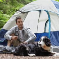 camper sitting in front of tent with dog