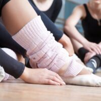 dancers sitting on floor with dance shoes showing