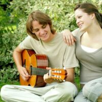 guy playing guitar with girl