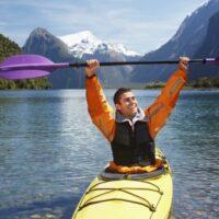 kayaker holding paddle on mountain lake