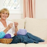 lady knitting on couch with balls of yarn