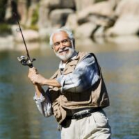 man fly fishing on river bank