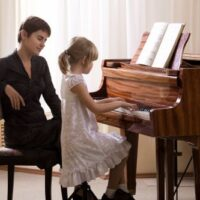student and piano teacher at a piano