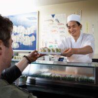 sushi chef handing food to customer