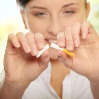woman breaking cigarette with her fingers, symbolic of quitting smoking